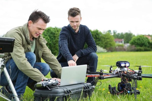 Coach and trainee crouching over laptop in preparation for the flight of a drone