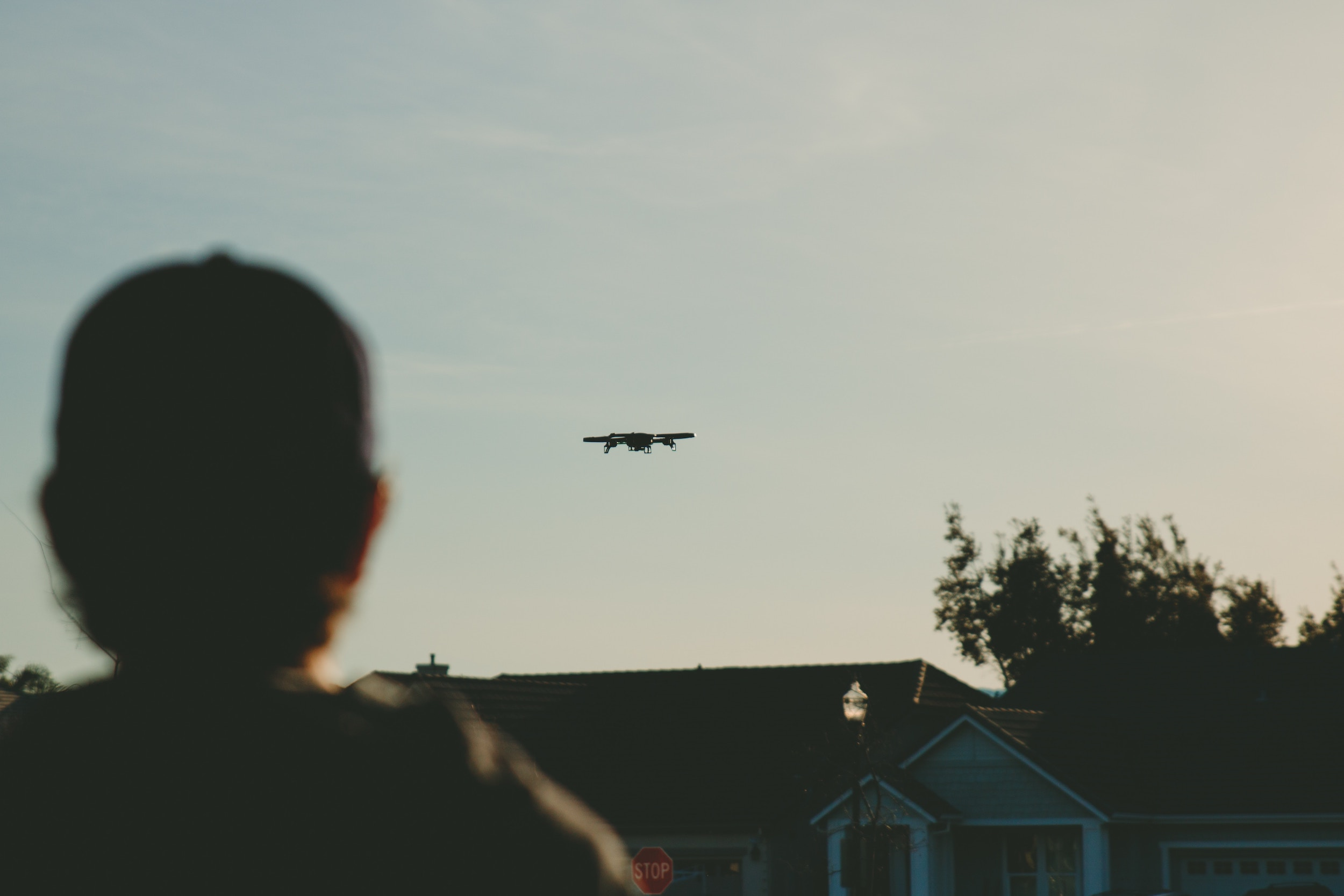 A drone, flying in to the sunset above houses. GVC Training by 3iC
